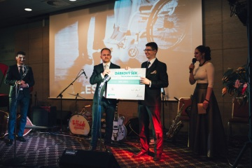 Zástupce společnosti TESCAN Maroš Karabinoš předává šek na 200 tisíc korun řediteli ParaCENTRA Fenix Michalu Odstrčilovi.