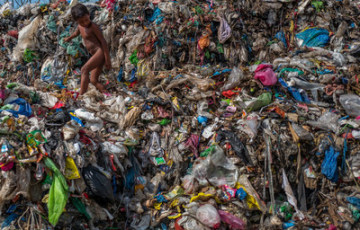 Credit: Orb Media.  A young boy climbs over plastic debris in a 50-year-old dump overlooking the ocean in the seaside town of Dagupan, Philippines. Most of the biodegradable items have long since rotted, leaving a mountain of multicolored plastics that float out to sea on the coastal winds.