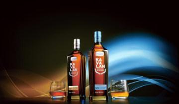 """Láhev whisky Kavalan ve tvaru budovy 101 pro řadu Kavalan Distillery Select Series symbolizuje základní silné stránky výběru a umění míchání. Vlevo """"Kavalan Distillery Select No. 1"""" je plná vůně ovoce propojené se smetanovými a karamelovými tóny. Vpravo """"Kavalan Distillery Select No. 2"""", v níž se mísí květinové a bylinné tóny, vyzrálá dřevnatost a teplá kořeněnost."""